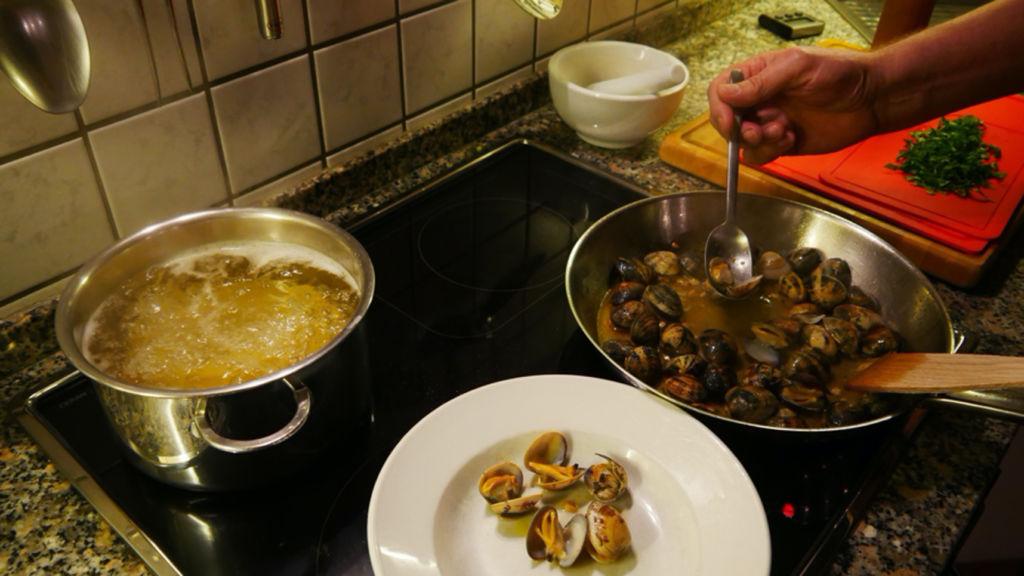 Zubereitung einer Muschel Pasta. Die Pasta wird in einem Topf gekocht und die Muscheln in einer Pfanne zubereitet.